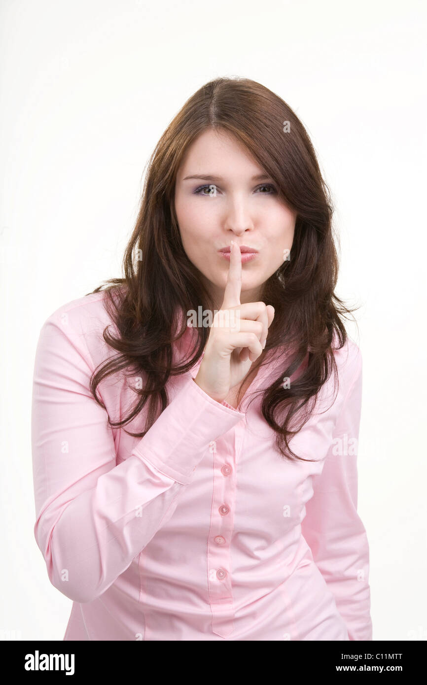 Young woman, gesturing for silence, secrecy - Stock Image