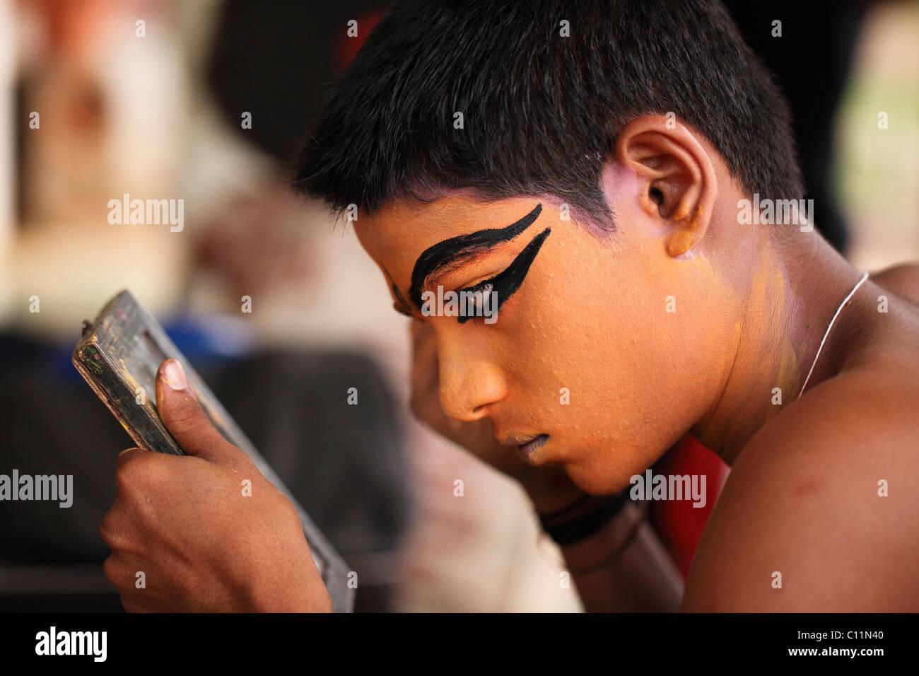 Kathakali dancer doing his make up, Minukku character, Kerala, southern India, Asia - Stock Image