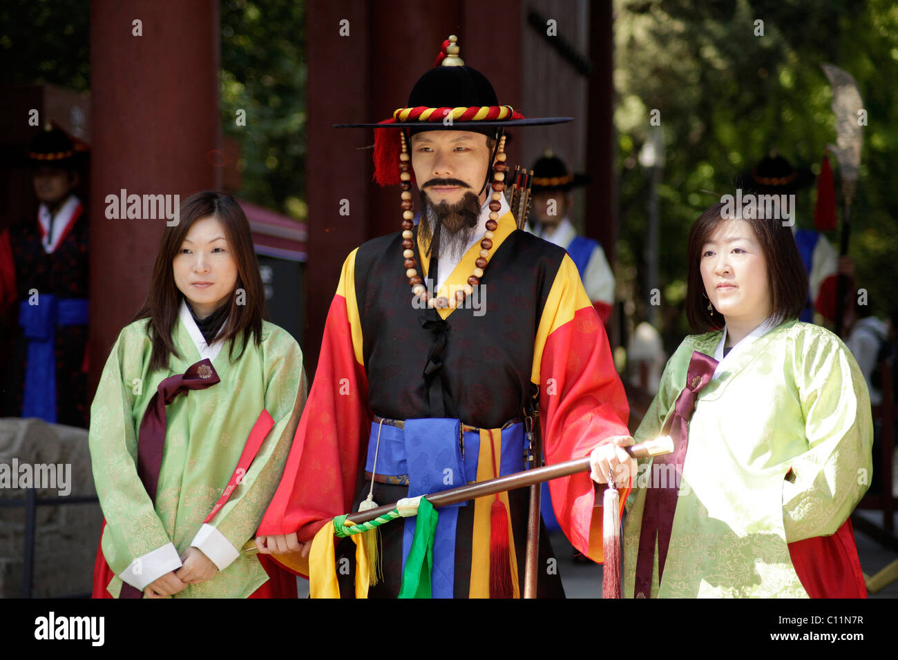 Young women posing with one of the guards in front of the Deoksugung royal palace, Palace of Longevity, in the Korean Stock Photo