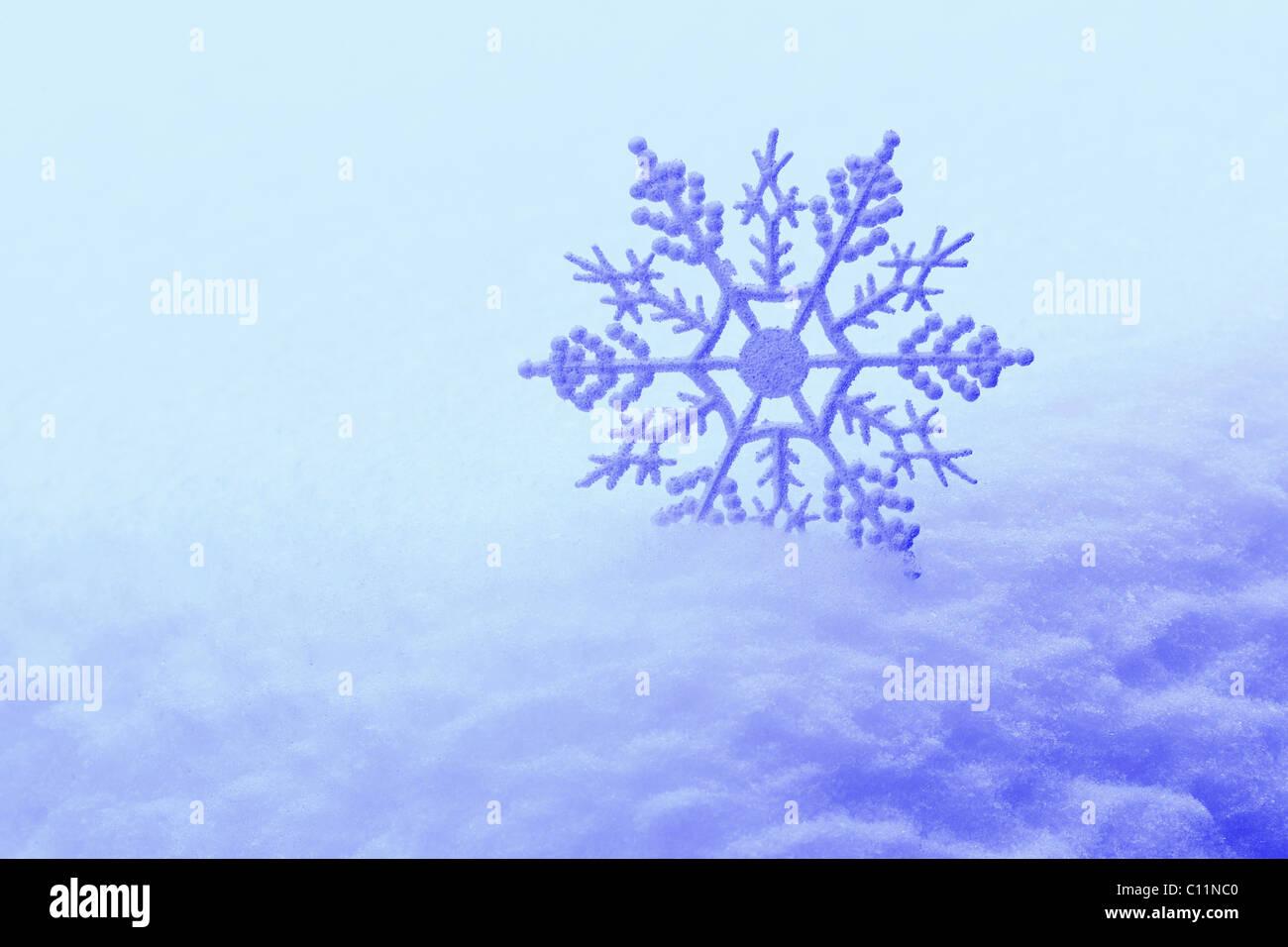 Decorative snowflake in snow Stock Photo