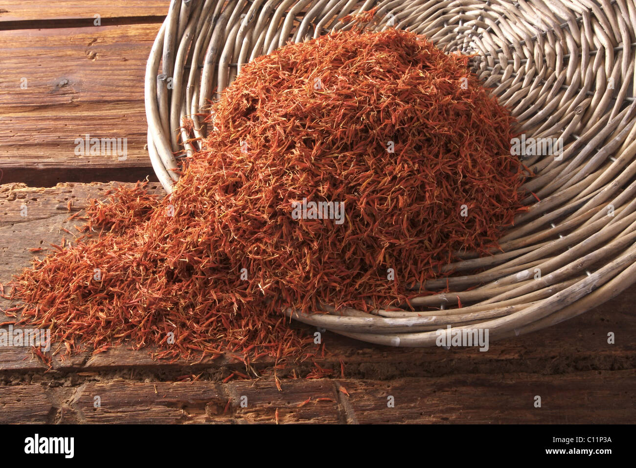 Safflower (Carthamus tinctorius), as tea or food coloring, saffron substitute, tipped out of a willow basket - Stock Image