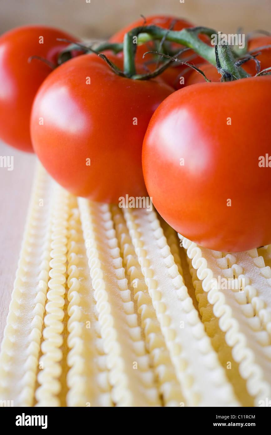 Raw pasta, tomatoes - Stock Image