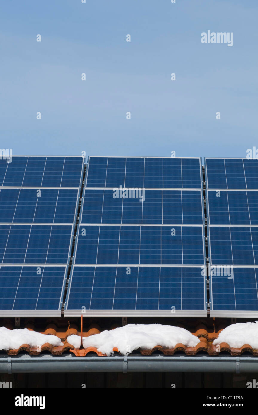 Solar panels on the roof of a house with patches of snow, renewable energy - Stock Image