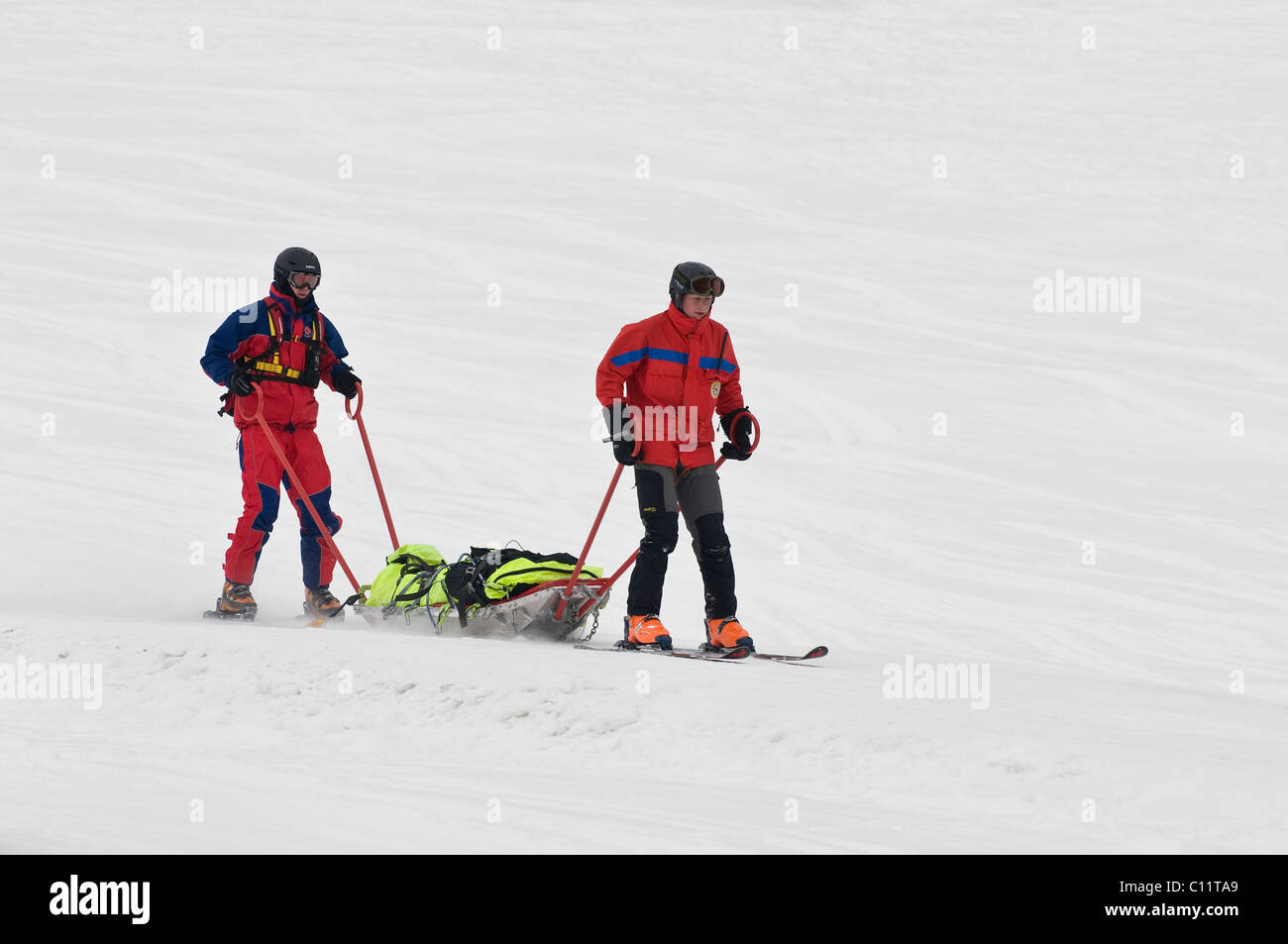 Mountain rescue service in operation, two rescuers on skis with a rescue stretcher skiing down to the valley, Chiemgau, - Stock Image