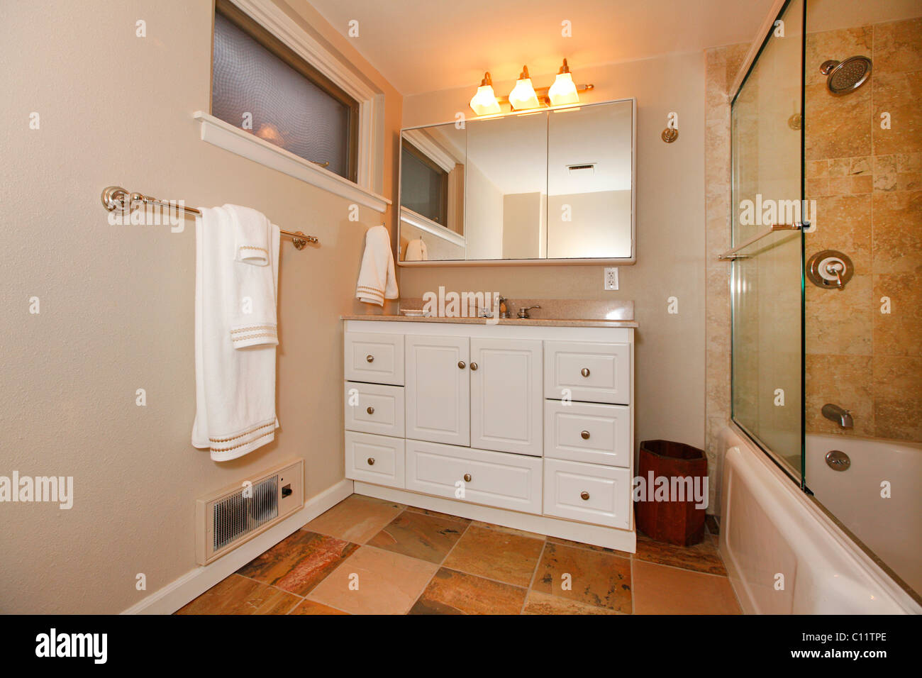 Classic beige bathroom with white and wood cabinets, tiles and beige walls. Tacoma, WA Stock Photo