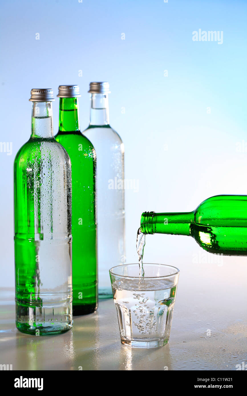 Mineral water bottles and a glass of water, drinking water - Stock Image