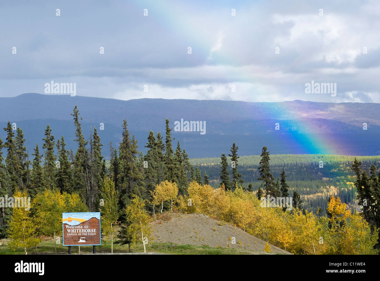 Rainbow, Indian Summer, trees in fall colours, Whitehorse welcoming sign, Two Mile Hill, Whitehorse, capital of - Stock Image