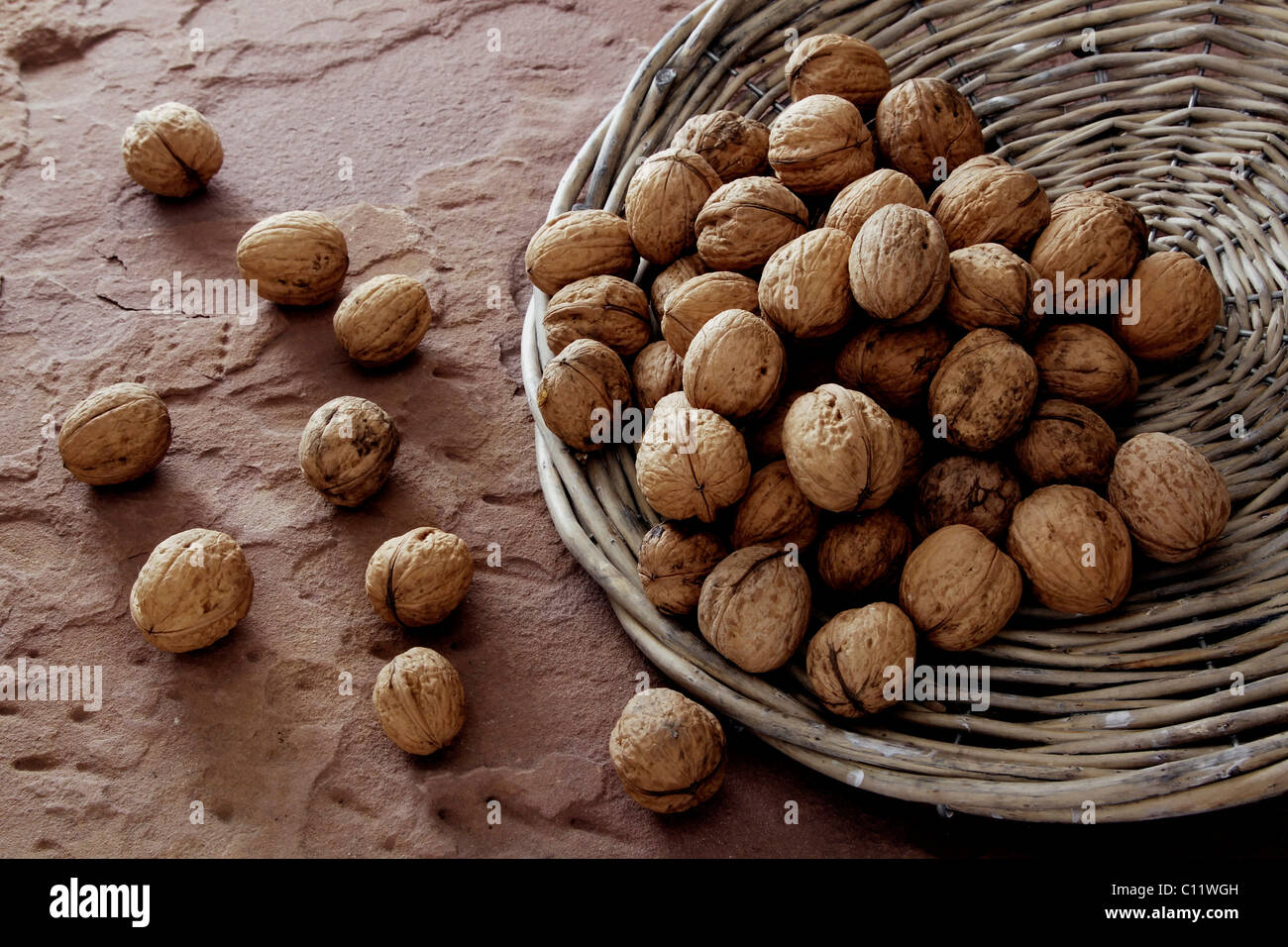Walnuts (Juglans) tipped from a wicker plate on sandstone Stock Photo