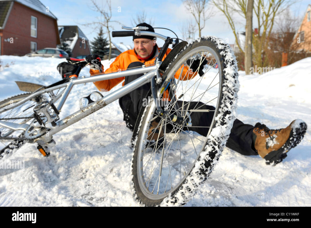 Cyclist crashing on a snow-covered slippery road - Stock Image