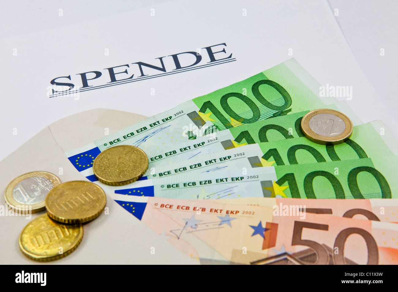 Envelope with euro banknotes and coins for a donation - Stock Image