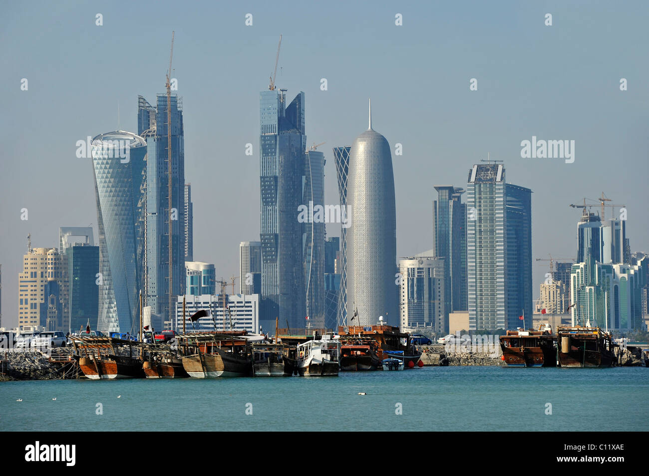 Tradition and modernity, dhow wooden cargo ships in front of the skyline of Doha, Qatar, Persian Gulf, Middle East, - Stock Image