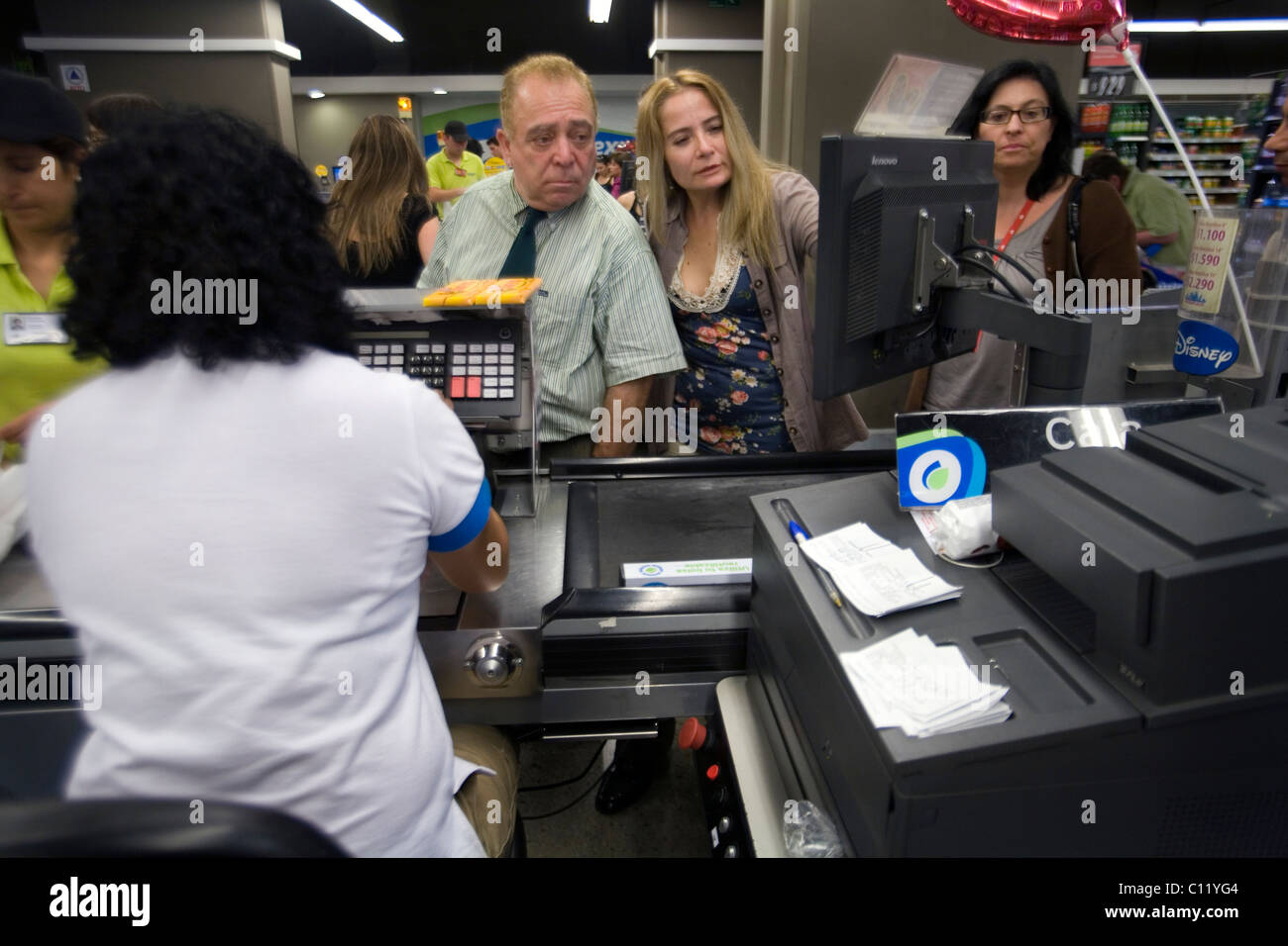 People looking at till display in a supermarket, Santiago de Chile - Stock Image