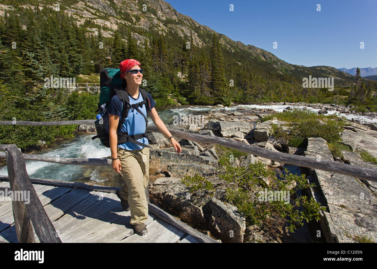 Young woman hiking, backpacking, crossing a wooden bridge, hiker with backpack, historic Chilkoot Pass, Chilkoot - Stock Image