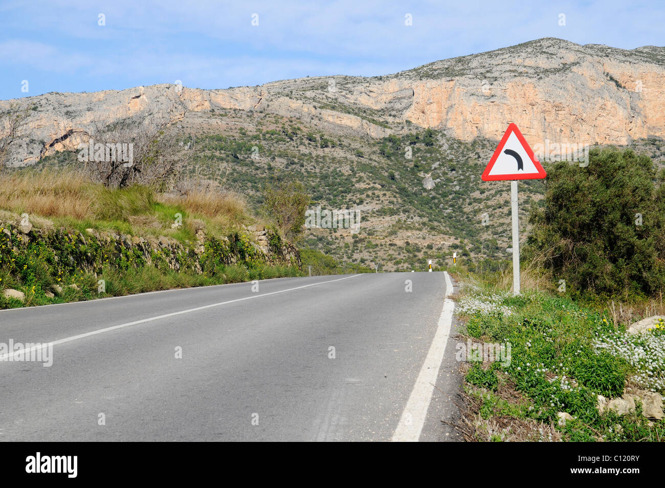 Bend, road, road sign, mountains, Javea, Costa Blanca, Alicante province, Spain, Europe - Stock Image