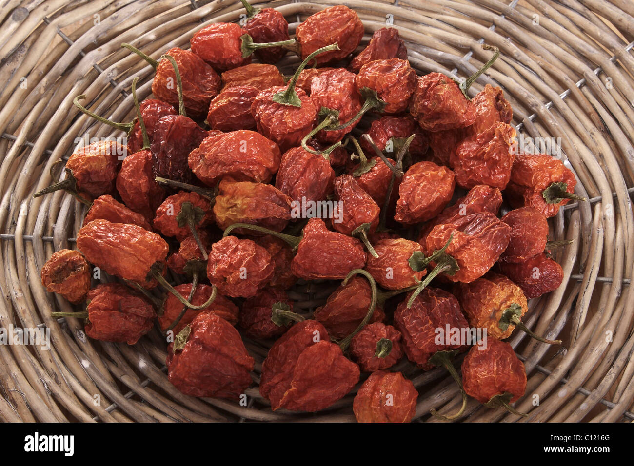 Dried mini peppers (capsicum) in a woven basket - Stock Image