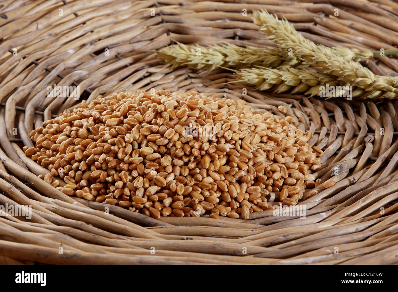 Wheat kernels (Triticum) with wheat ears in a woven basket - Stock Image