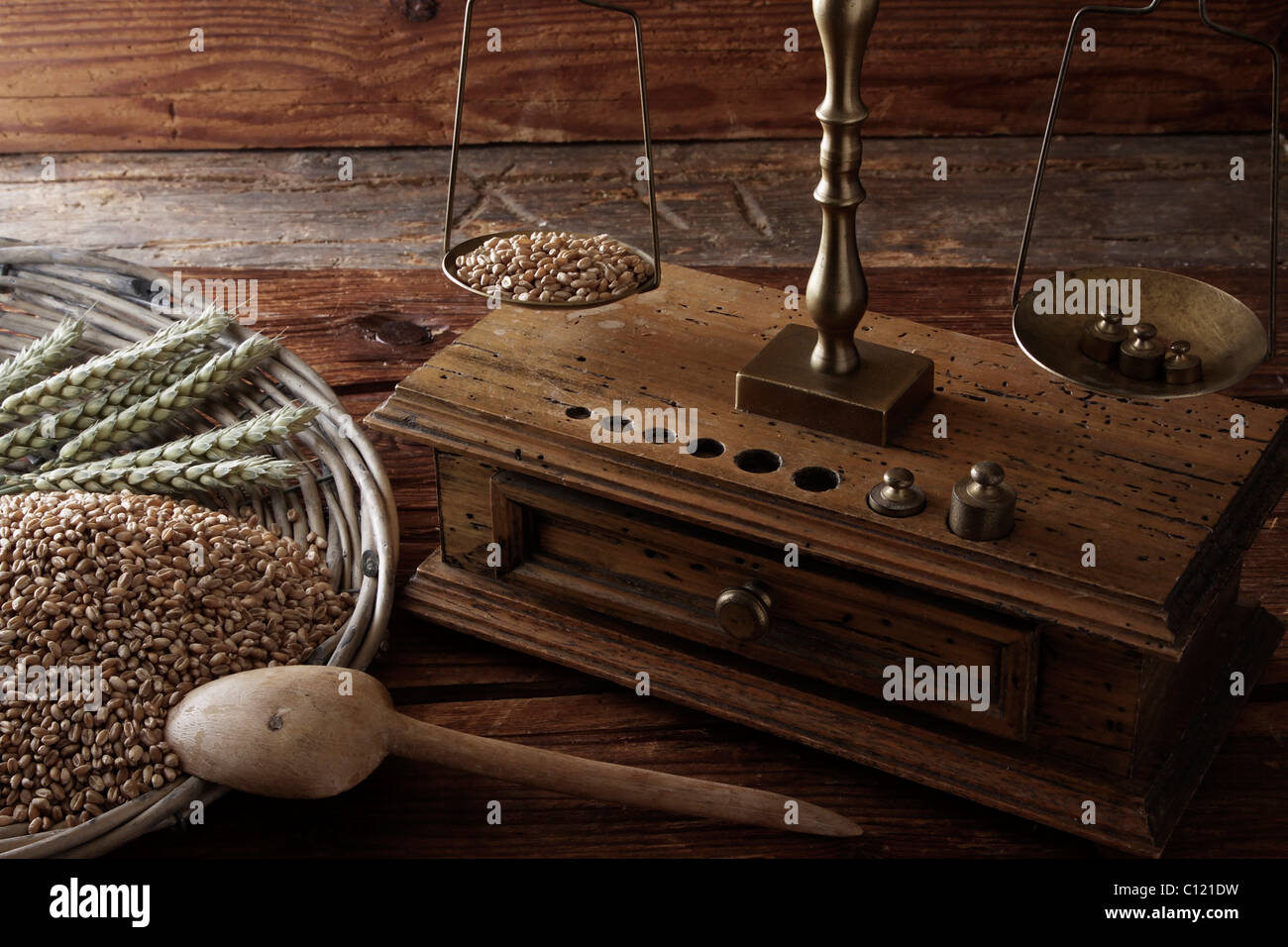 Antique scales weighing grains of Wheat (Triticum) - Stock Image