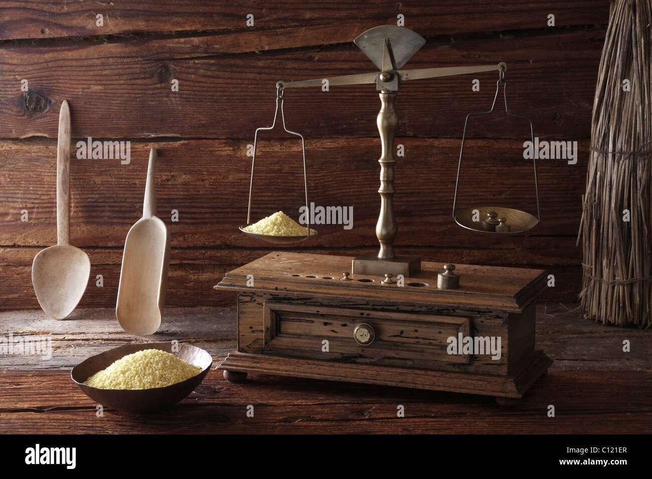 Antique scales weighing grains of Millet (Panicum miliaceum) on a wooden surface - Stock Image