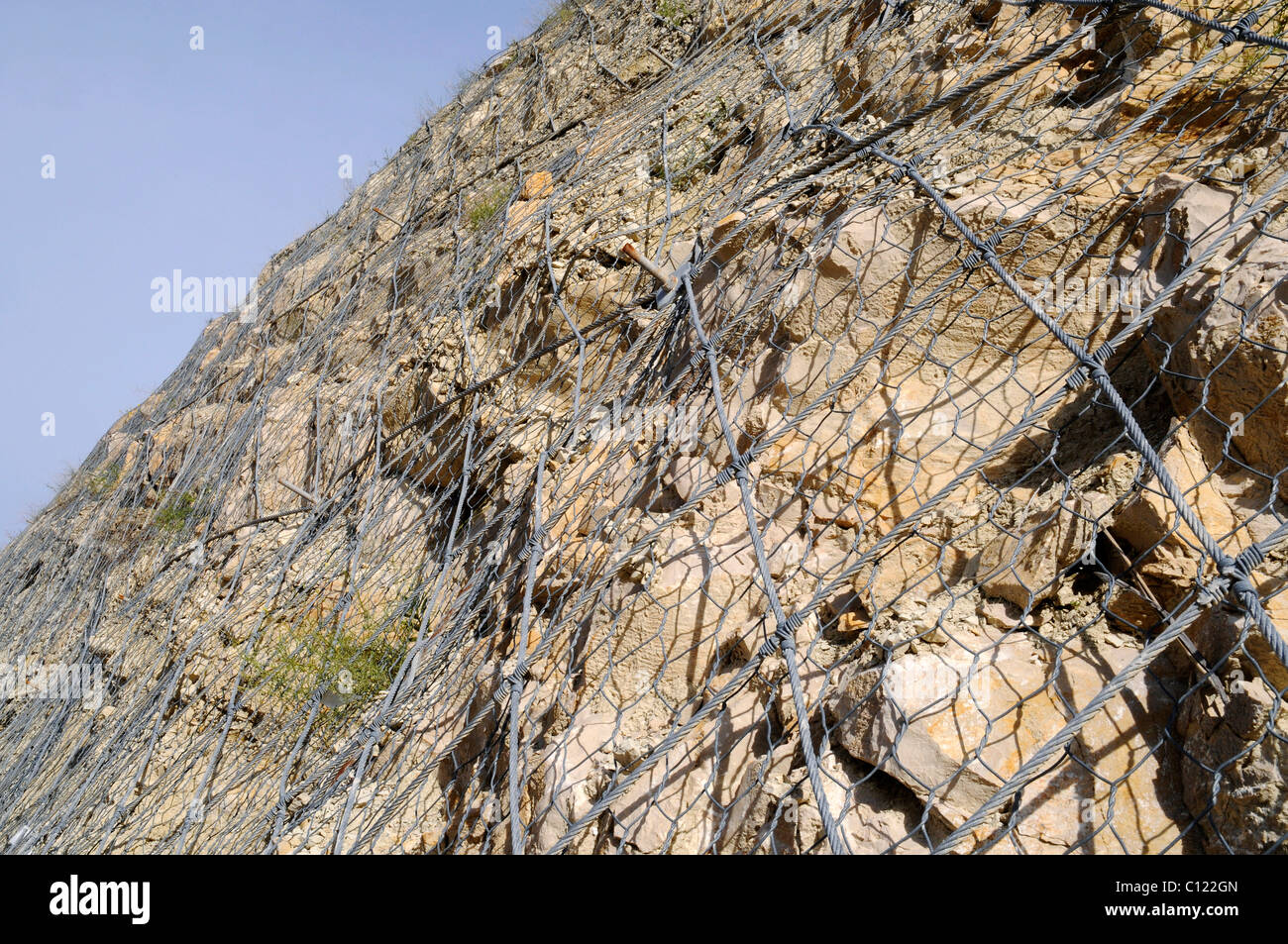 Wire mesh securing a slope from rockfall or landslide, Costa Blanca, Alicante province, Spain, Europe Stock Photo