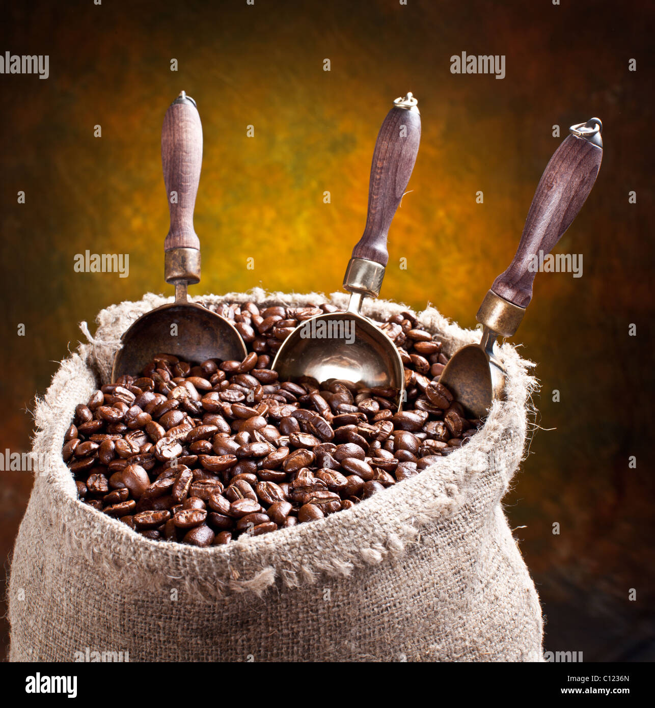 Sack of coffee beans and scoop. On a dark background. Stock Photo