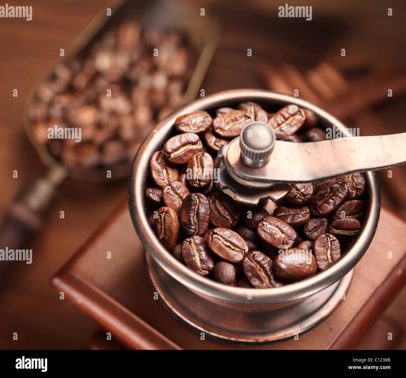 Roasted coffee beans are ground in a coffee grinder. - Stock Image