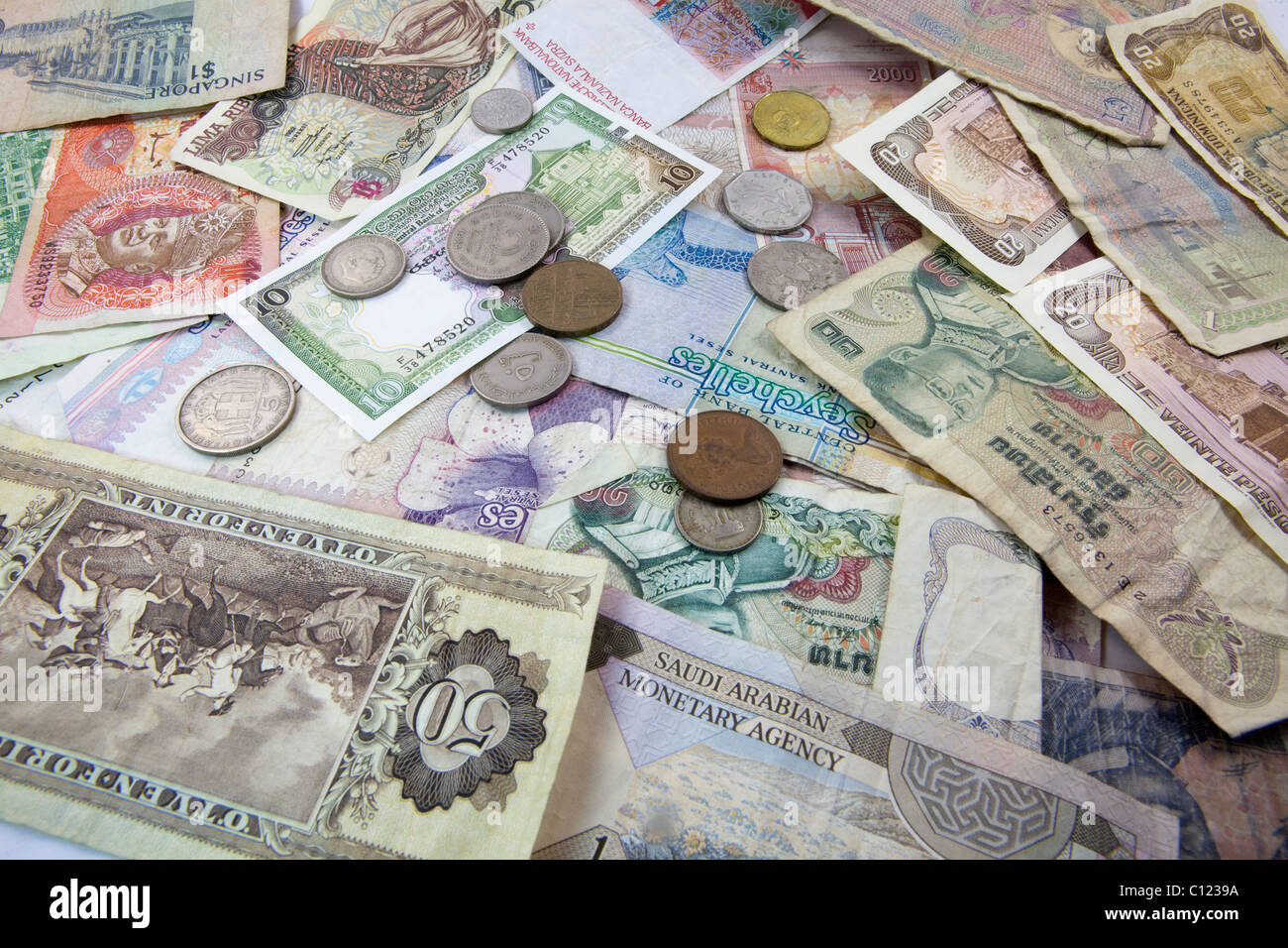 Banknotes and coins from different currencies - Stock Image