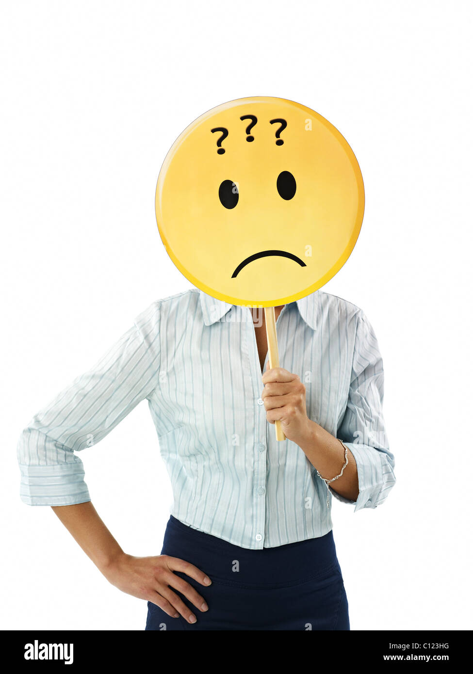 adult business woman holding emoticon with question marks on white background. Vertical shape, waist up - Stock Image