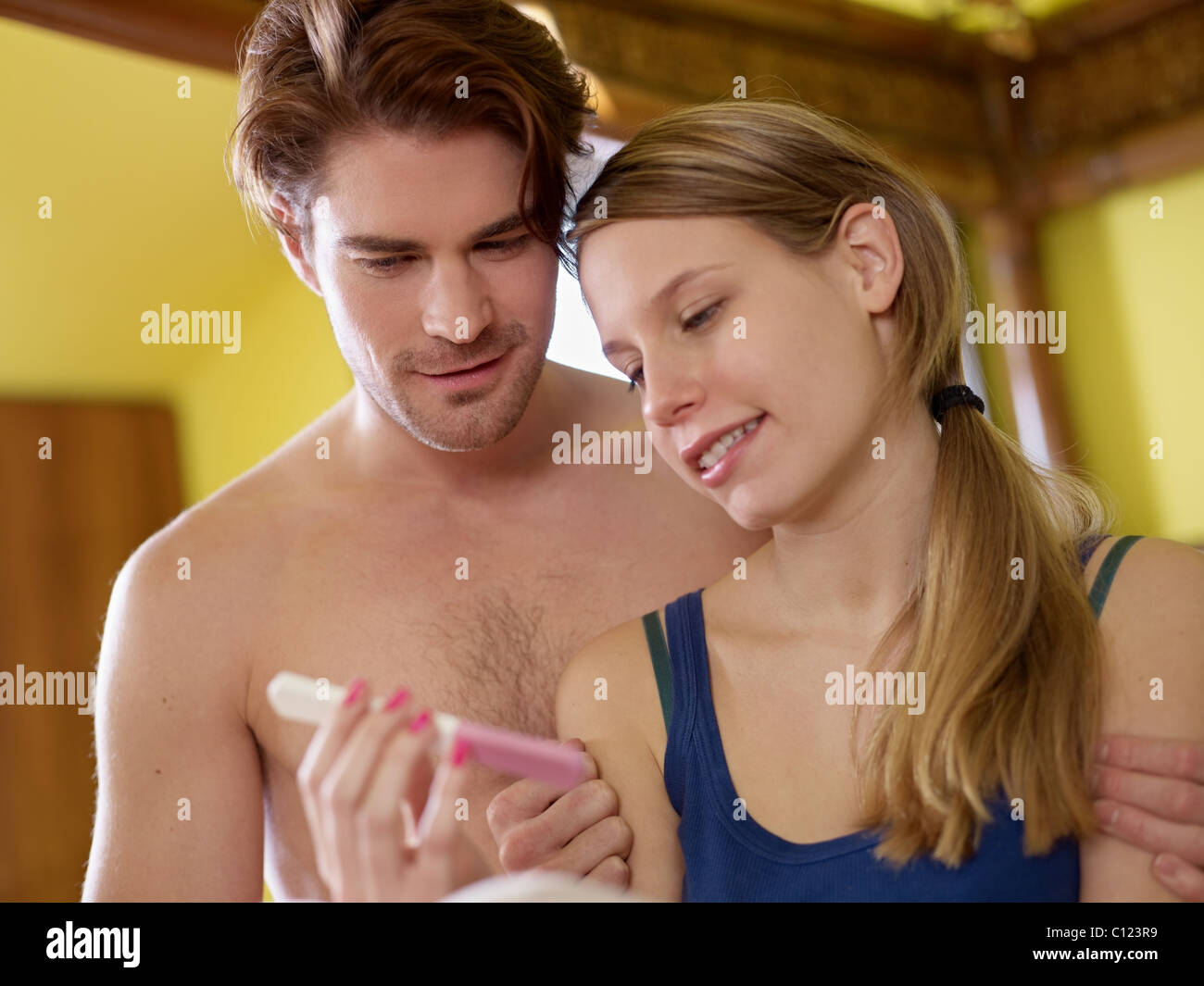young heterosexual couple looking at pregnancy test - Stock Image