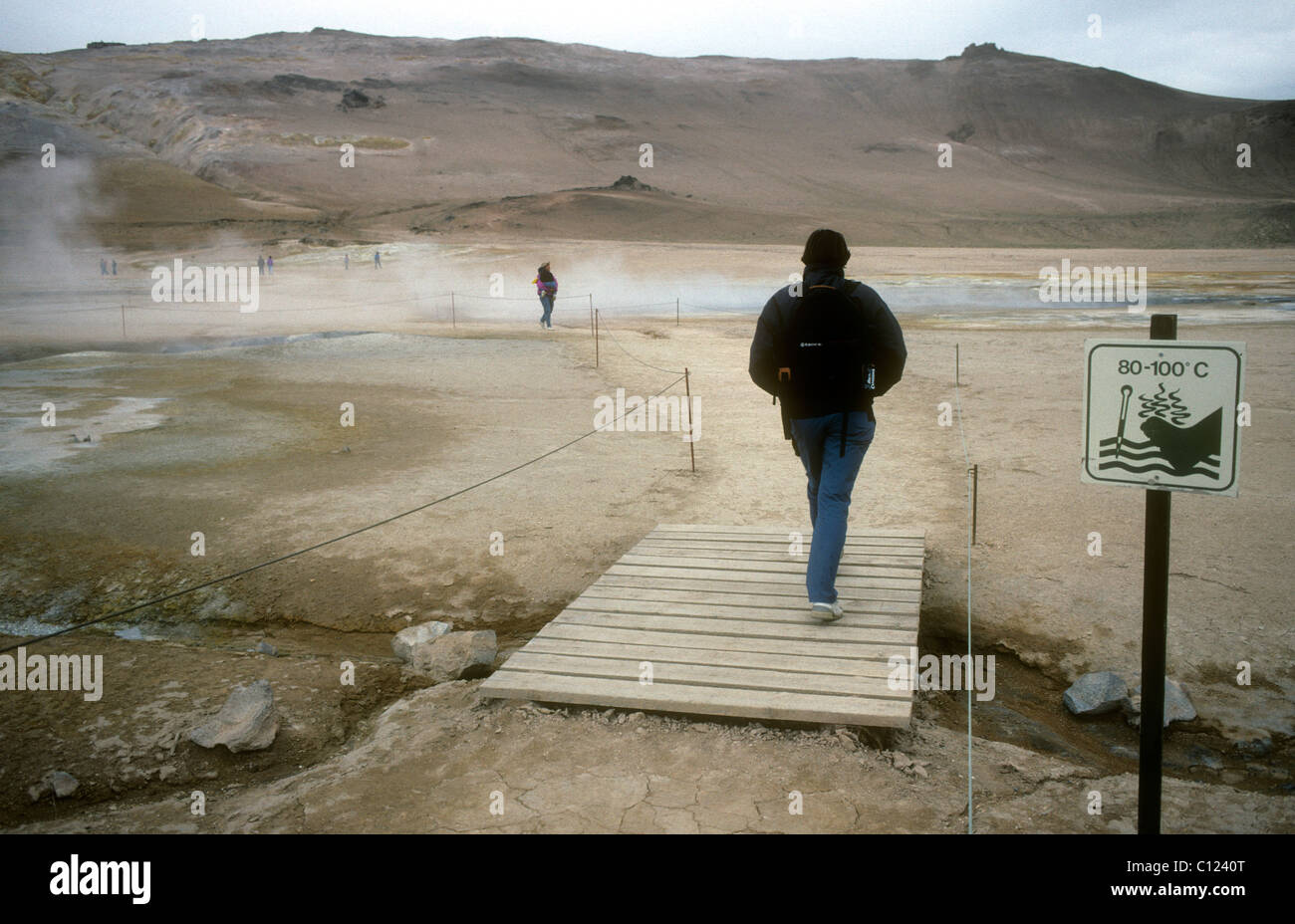 A tourist on a boardwalk passes a sign warning of very hot ground at the Namaskard solfatara field in northern Iceland Stock Photo