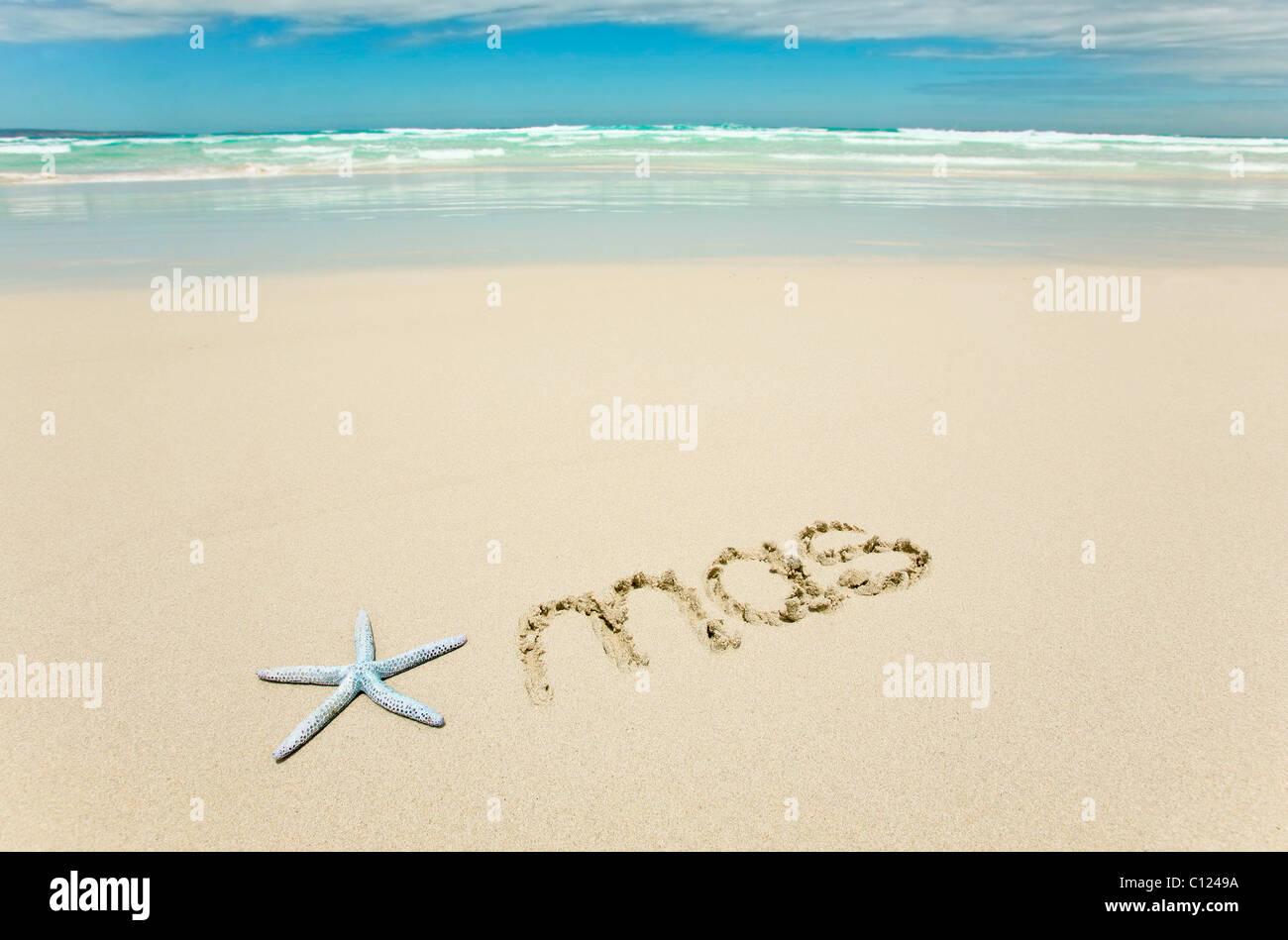 Xmas written on beach - Stock Image