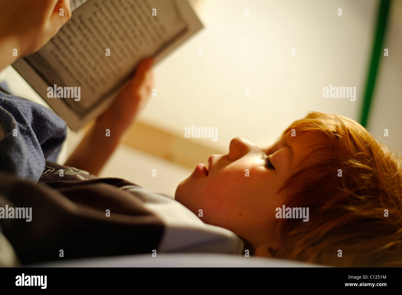 Child, boy reading in bed - Stock Image