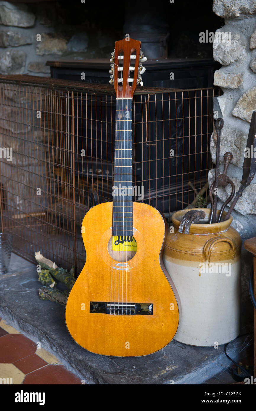 Acoustic guitar in front of a wood buring stove in the living room of a rustic house UK - Stock Image