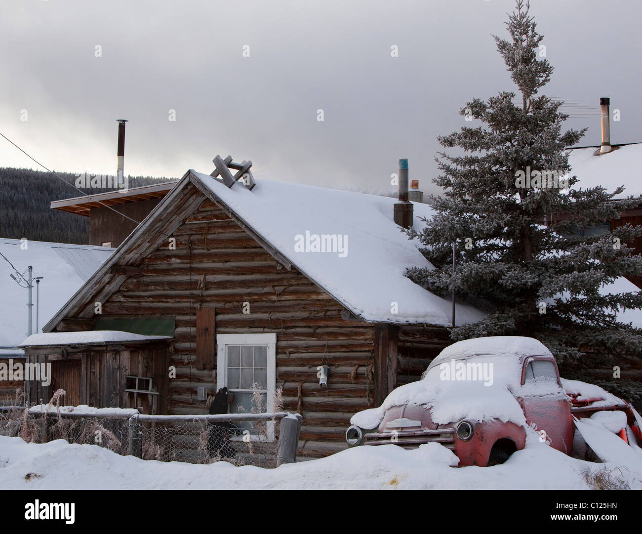 Old log house and old snow covered truck near lake bennett carcross yukon territory
