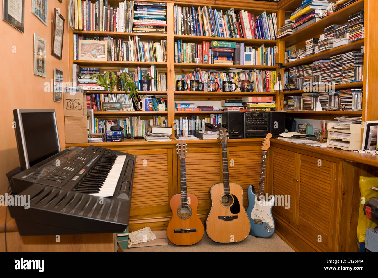 Study and music room with electric piano guitars and bookshelves in UK house - Stock Image