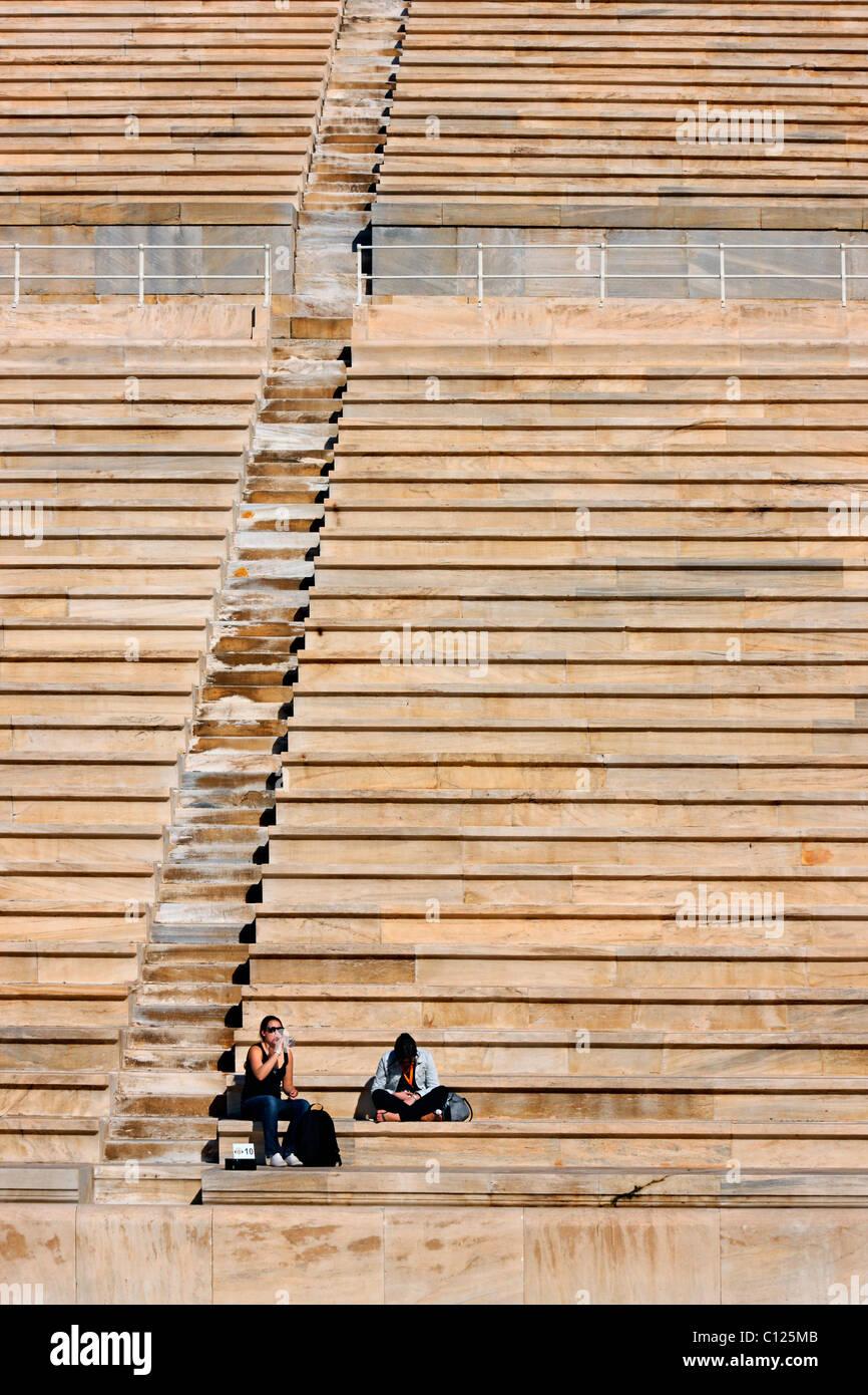"""Two young ladies resting during a tour around Kallimarmaro (""""Panathenaic"""") stadium, Athens, Greece Stock Photo"""