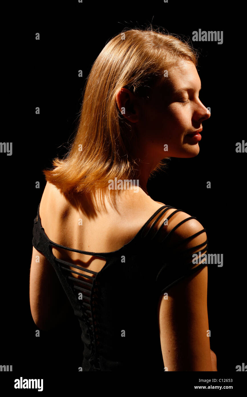 Young woman in a strapless top, back view - Stock Image