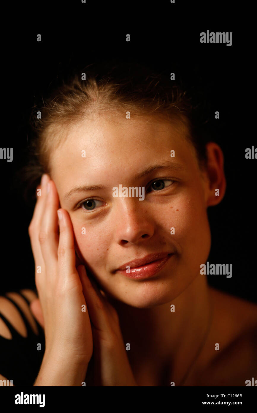 Young woman putting her hands to her face - Stock Image
