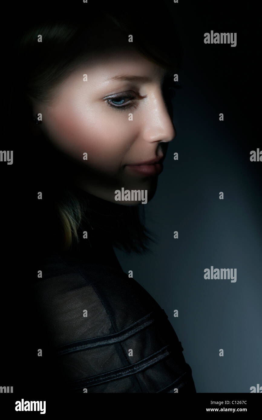 Side portrait of a young woman looking down - Stock Image