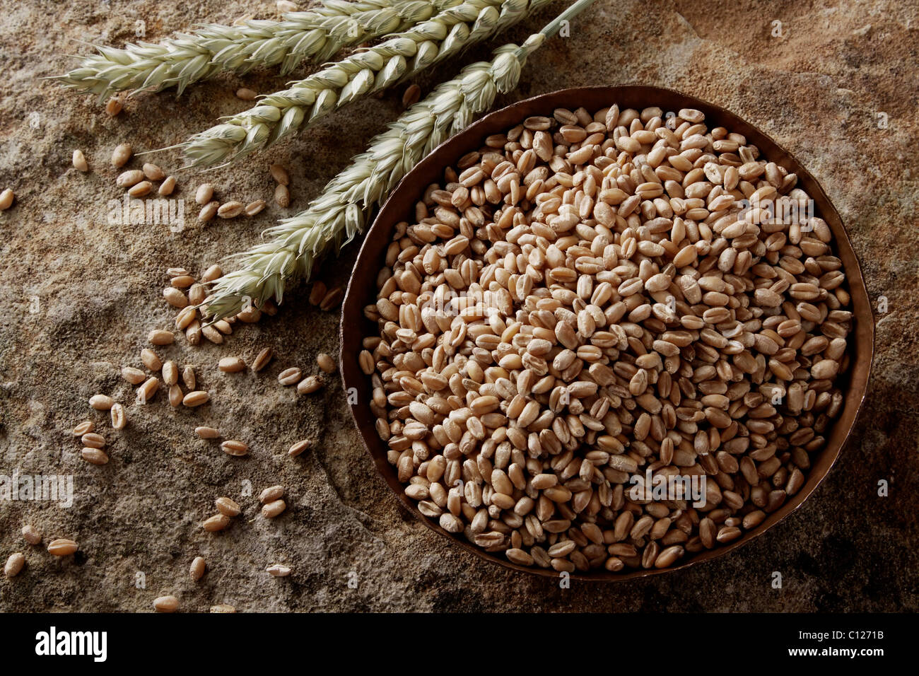 Wheat grains (Triticum) in a copper bowl on a stone surface Stock Photo