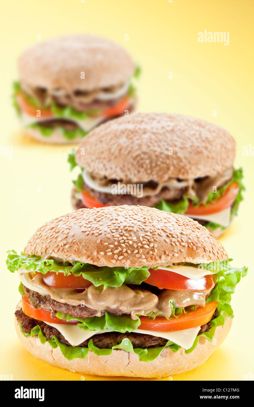 Three delicious hamburger on a yellow background - Stock Image