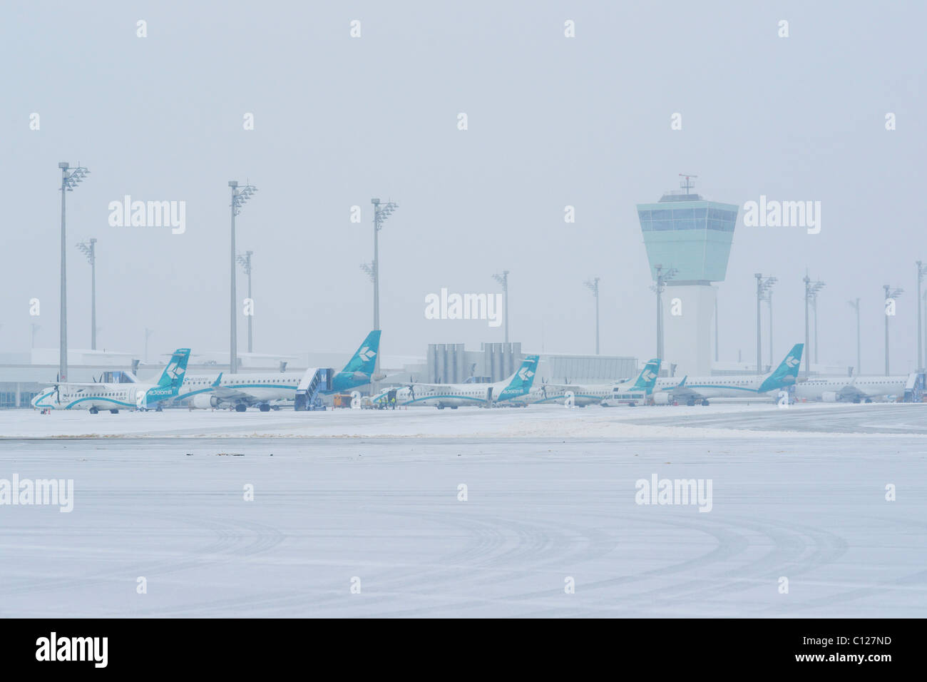 Snow, winter, Air Dolomiti airplanes, control tower, east apron, Munich Airport, MUC, Bavaria, Germany, Europe - Stock Image