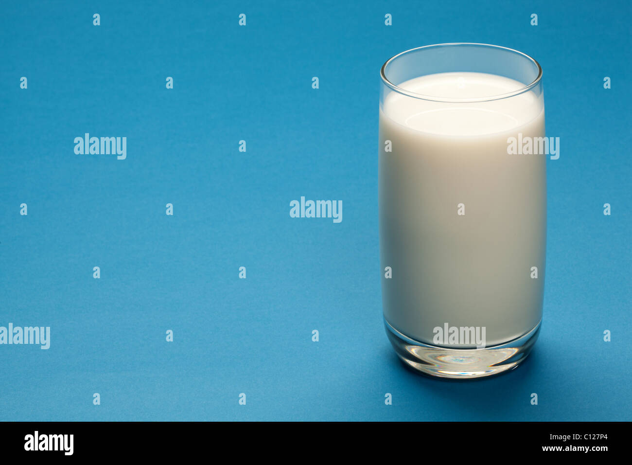 Glass of milk on a blue background. - Stock Image
