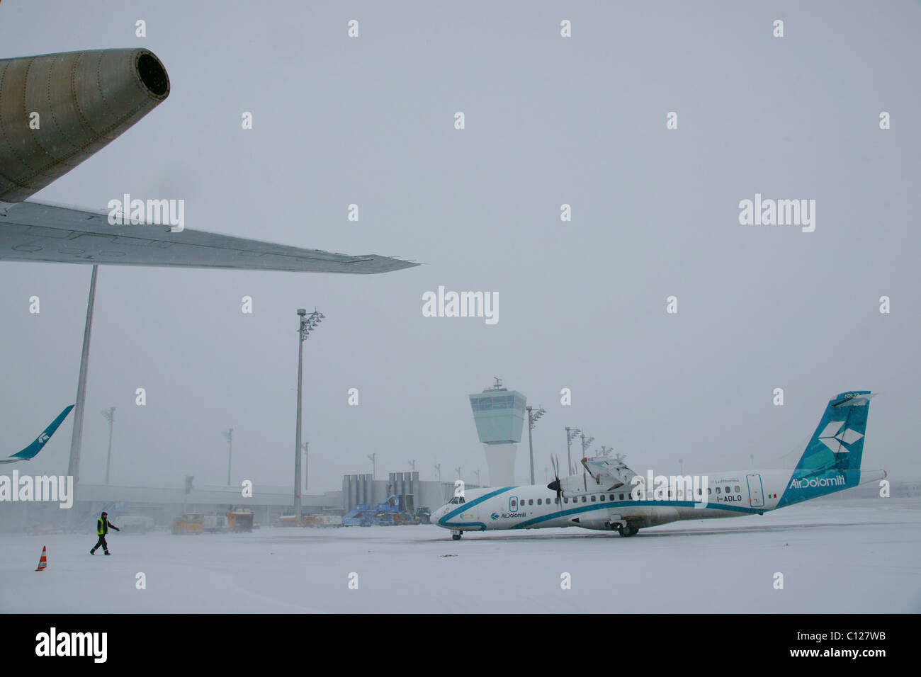 Snow, winter, roll out, Air Dolomiti airplane, control tower, east apron, Munich Airport, MUC, Bavaria, Germany, - Stock Image