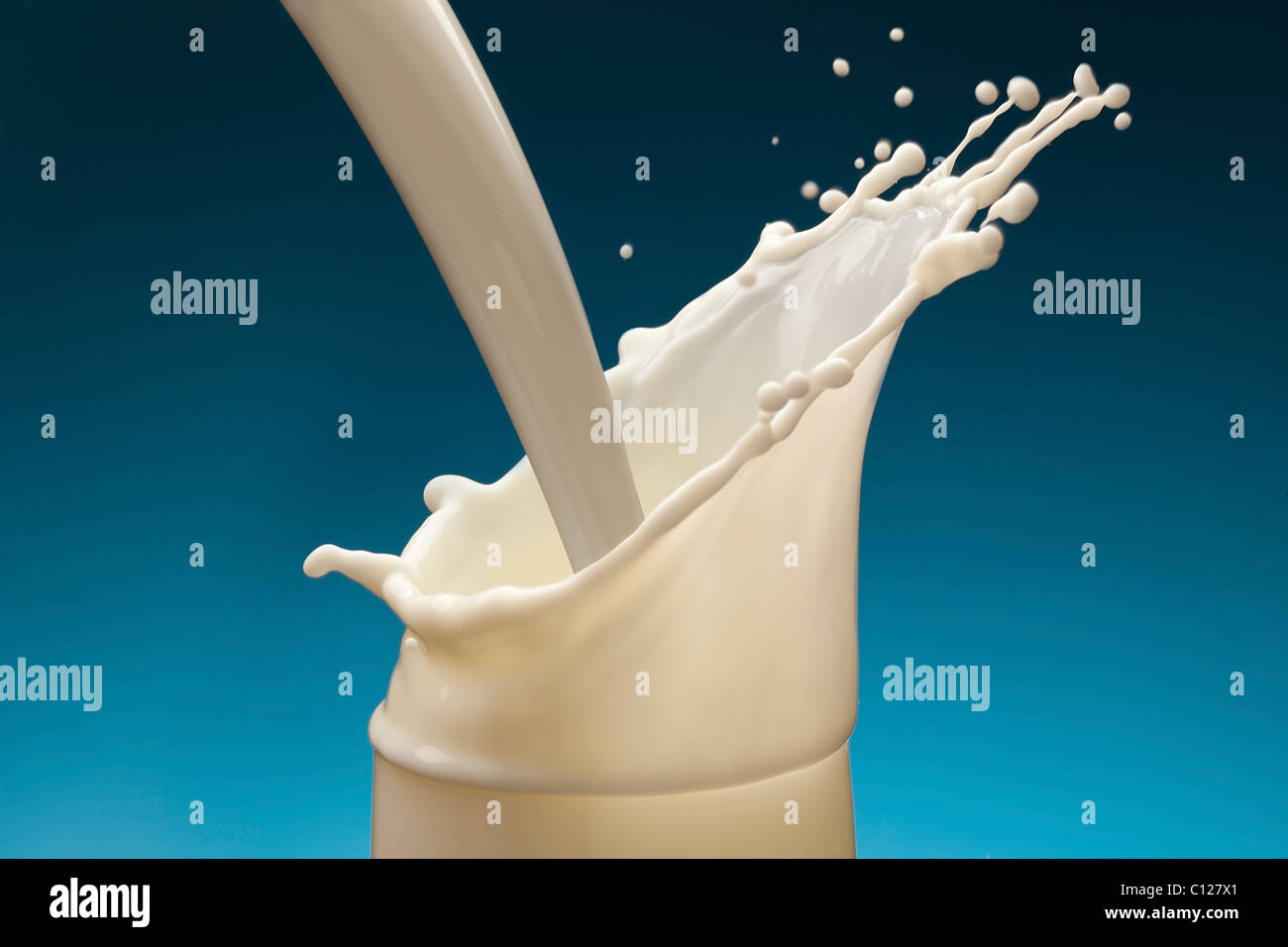 Splash of milk from the glass on a blue background - Stock Image