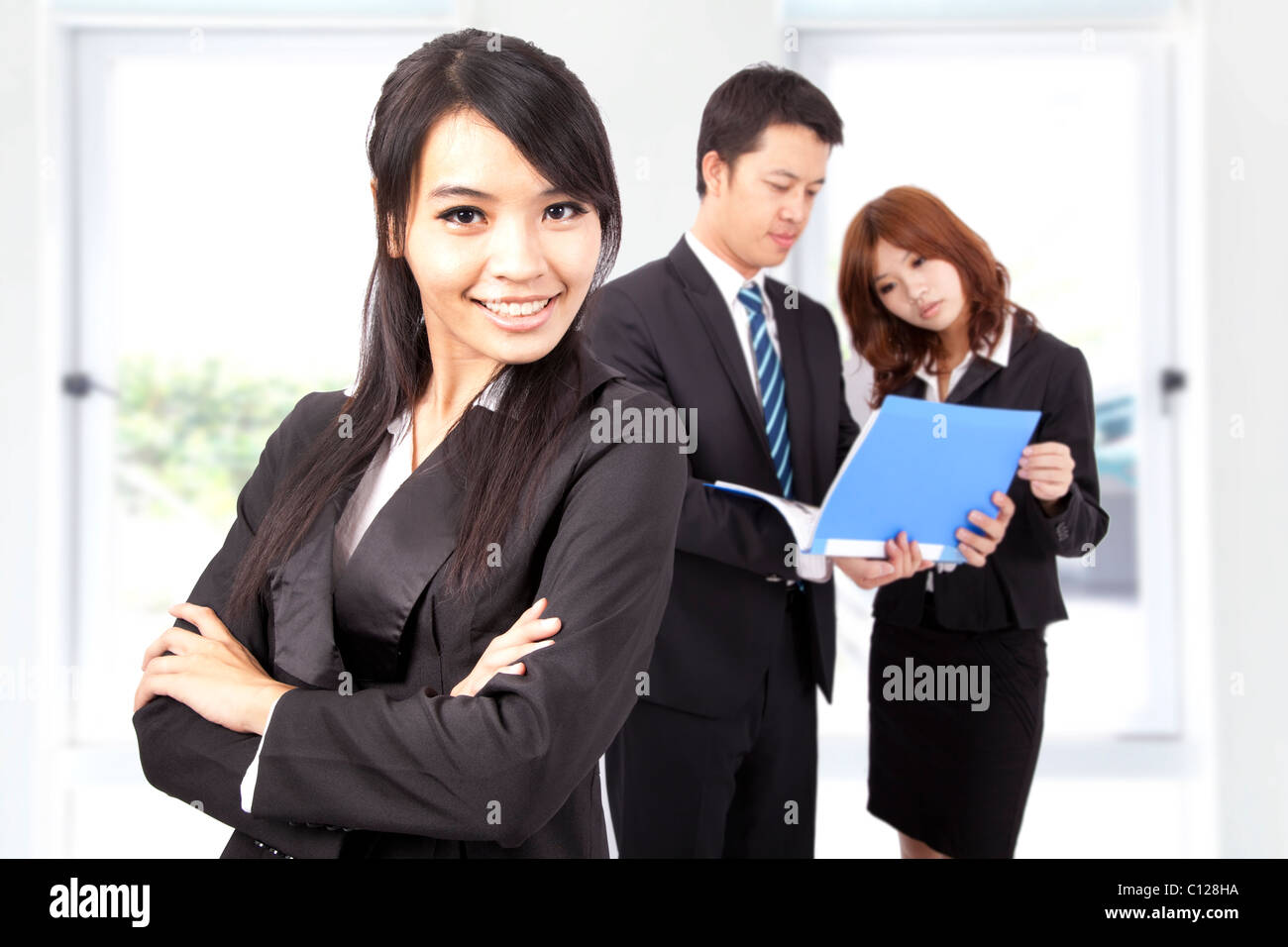 Young and smiling Business woman in an office - Stock Image