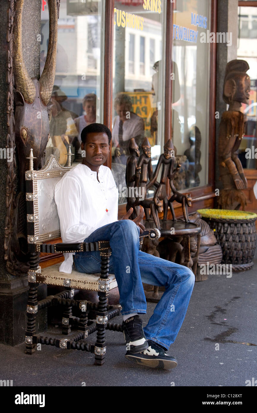 Arts and crafts shop, Africans sitting in front of the shop on Long Street, Cape Town, Western Cape, South Africa, - Stock Image