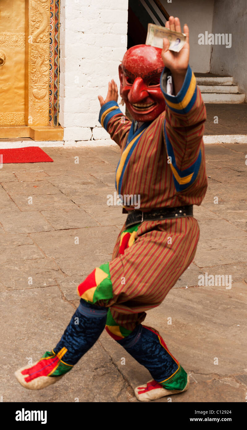 Bhutanese festival joker who plays pranks on visitors and raises money from onlookers. - Stock Image