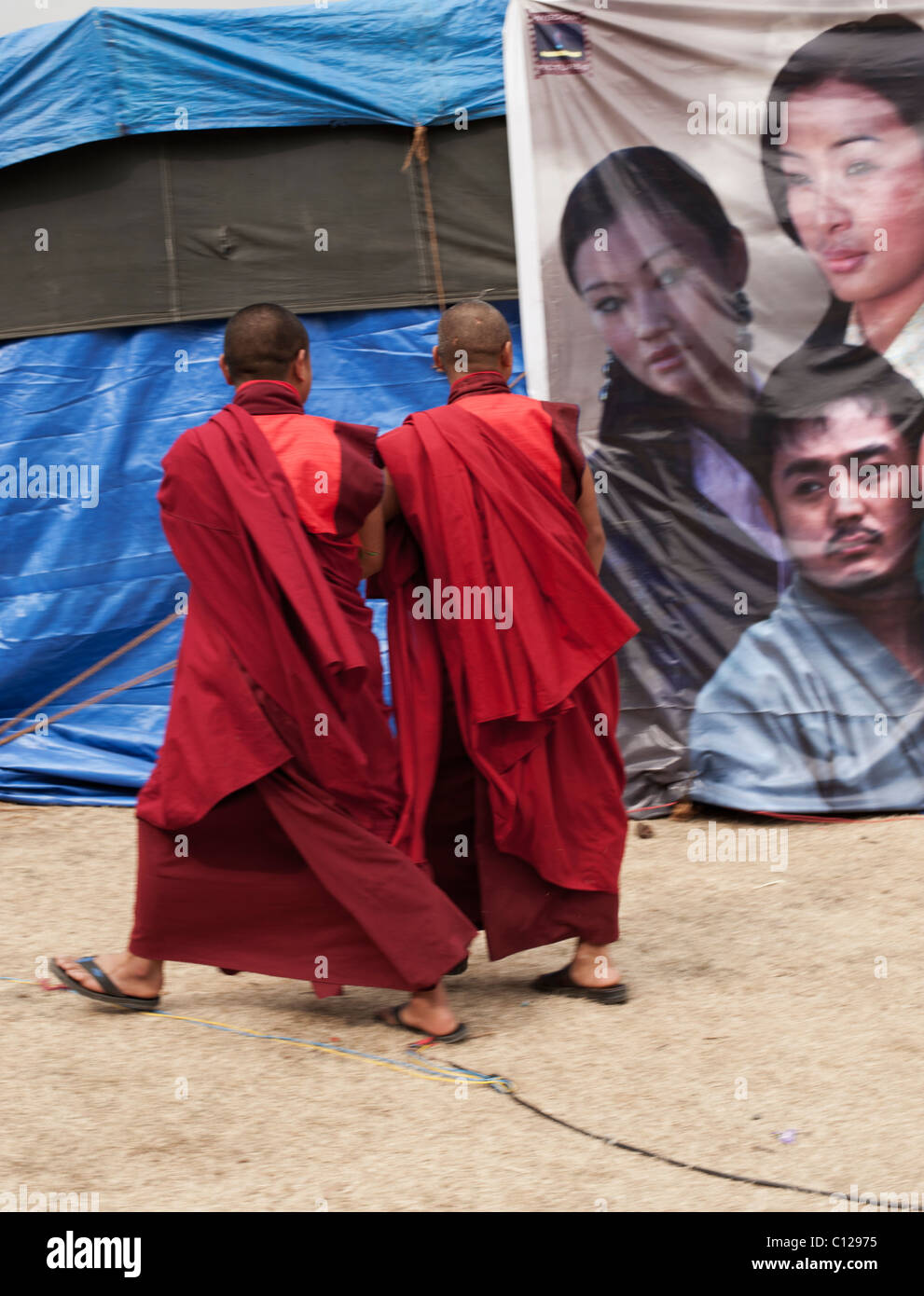 Buddhist monks ponder the virtues of buying a ticket to a new film being shown in a tent at a festival in rural Stock Photo