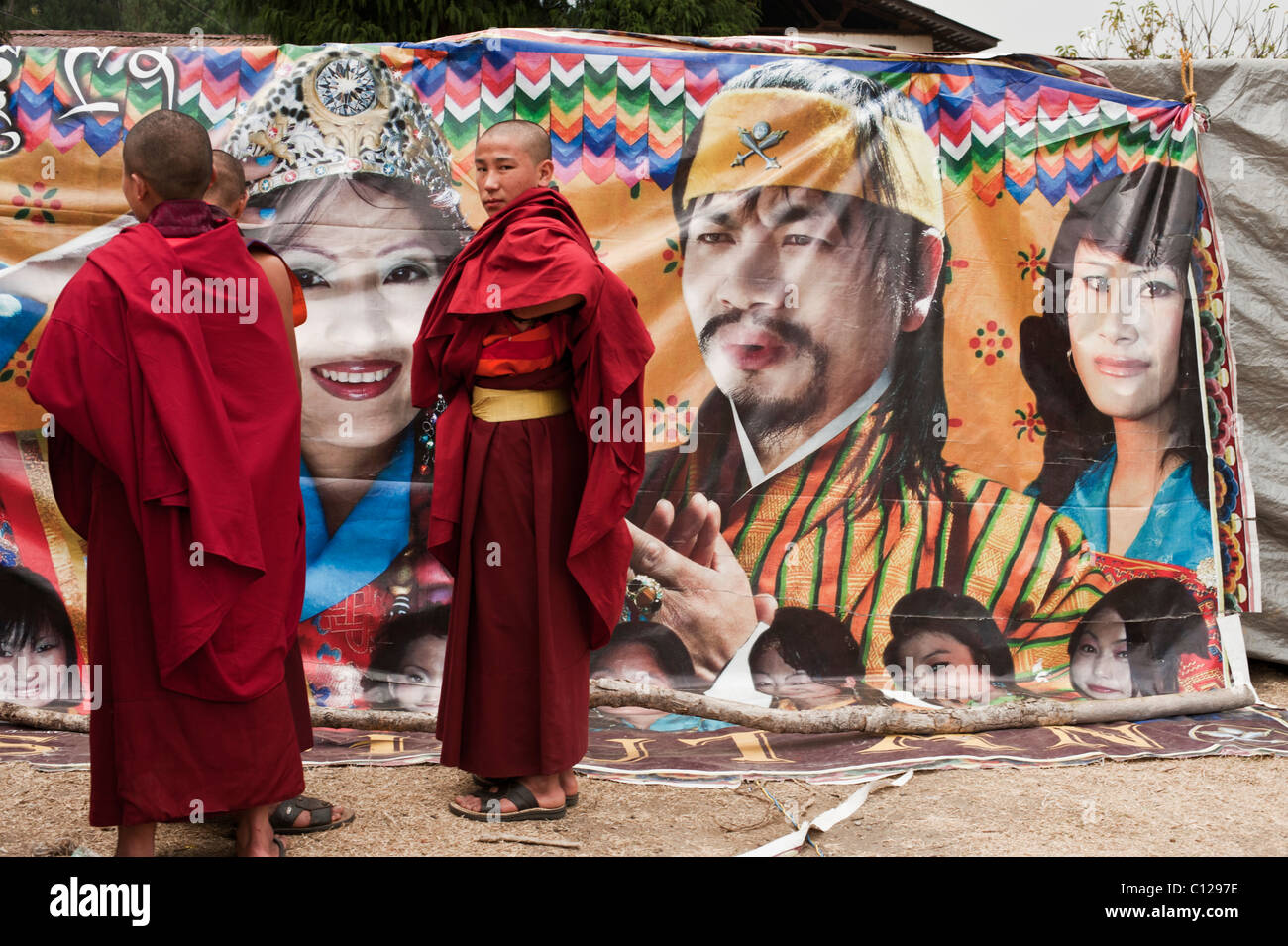 Buddhist monks ponder the virtues of buying a ticket to a new film being shown in a tent at a festival in rural - Stock Image
