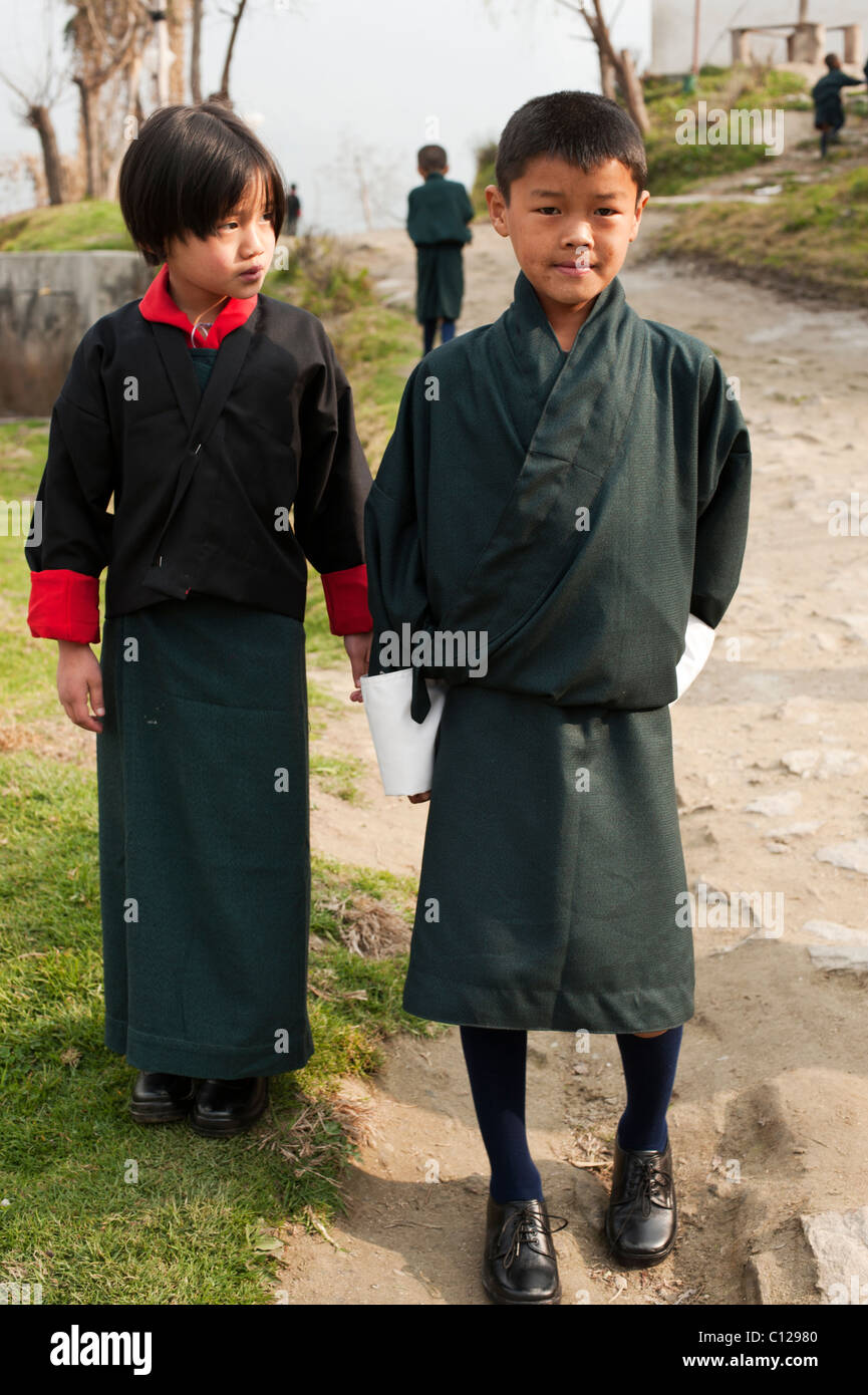Young Bhutanese boy and girl on their way to the first day of school in rural Bhutan dressed in school uniforms - Stock Image